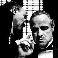 American actor Marlon Brando (1924 - 2004) listens as an unident